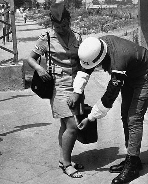 No hay lugar para la minifalda en el ejército. Un policía militar israelí mide la distancia entre la rodilla y la falda de una compañera para comprobar que no sea mayor de 3 centímetros.