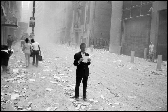 USA. NYC. 9/11/2001. A dazed man picks up a paper that was blown out of the towers after the attack of the World Trade Center, and begins to read it. Via
