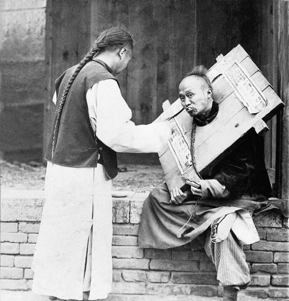 Chinese man feeding a criminal in a cangue with a sign describing his crime, 1905. Via